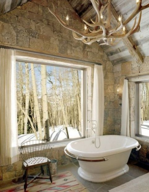 a stone clad bathroom design  with a view