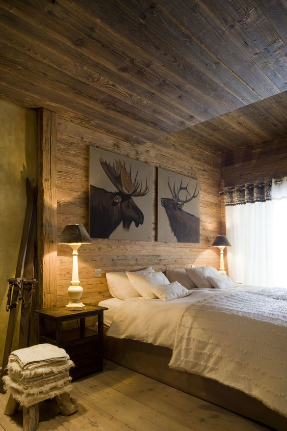 a cozy chalet bedroom all clad with wood, with vintage-inspired furniture, a pair of artworks and even skis