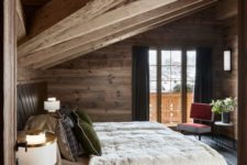 a cozy chalet bedroom clad with wood, with upolstered furniture, chic lamps and an entrance to the balcony