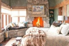 a cozy chalet bedroom with a stone clad fireplace, a vintage bed, a vintage chandelier, a stone bench and wooden stools