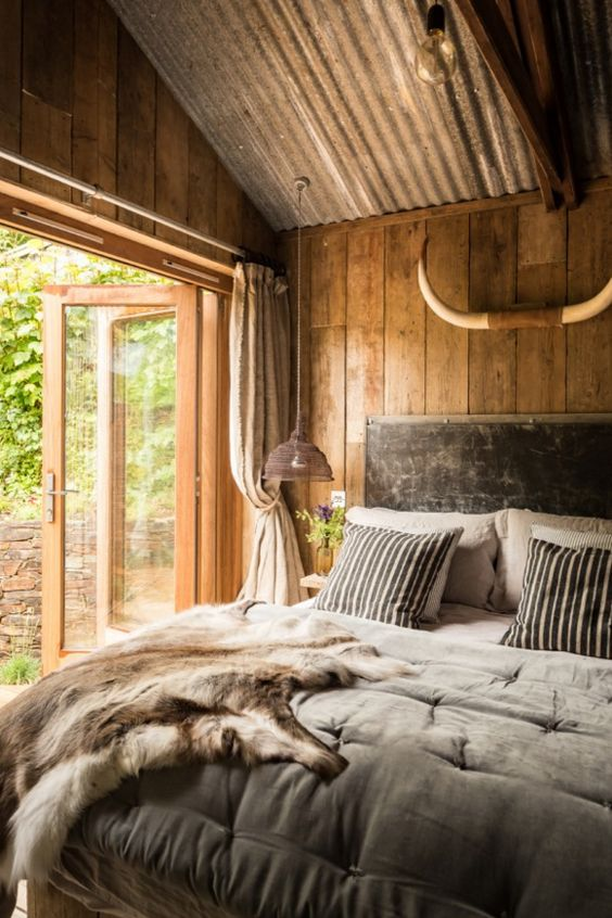 a cozy chalet bedroom with wood, a corrugated steel ceiling, simple furniture and grey bedding plus an exit outside