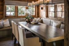 a cozy chalet dining space with a corner sofa, a wooden table, some modern chairs, a pendant candle holder is welcoming