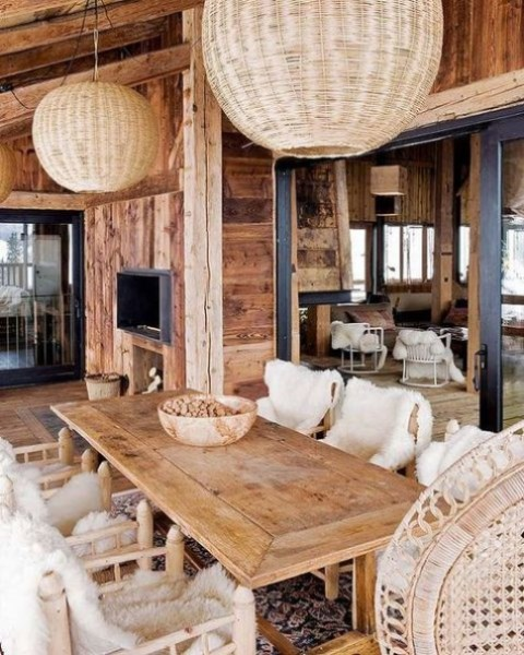 a cozy chalet dining space with a rustic table and chairs, wicker pendant lamps, faux fur and a boho rug