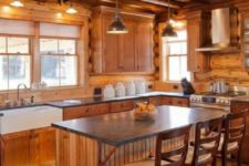 a cozy chalet kitchen all clad with wood, with blakc stone countertops, metal pendant lamps, vintage stools