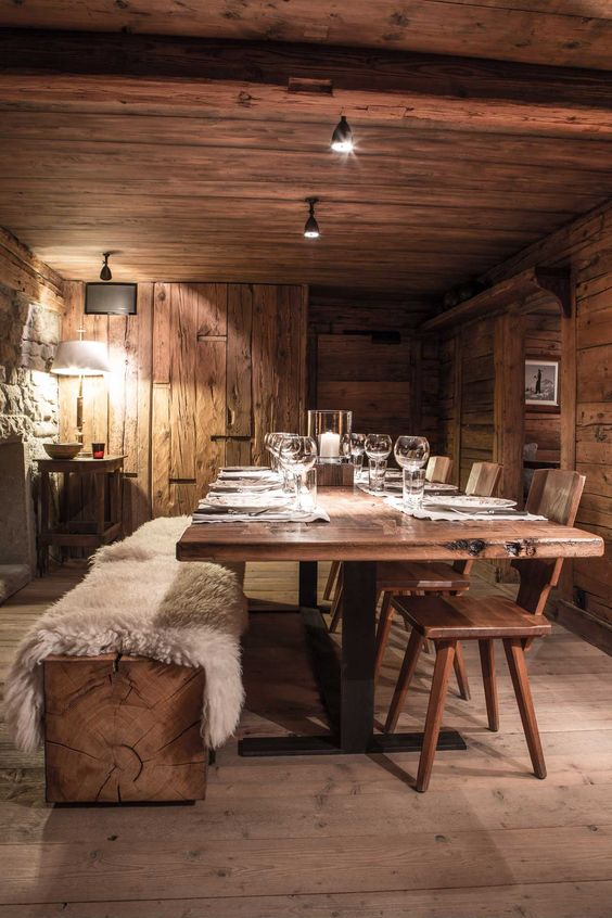 a cozy dining room with a wooden table and chair plus a slab as a bench, some lights and lamps
