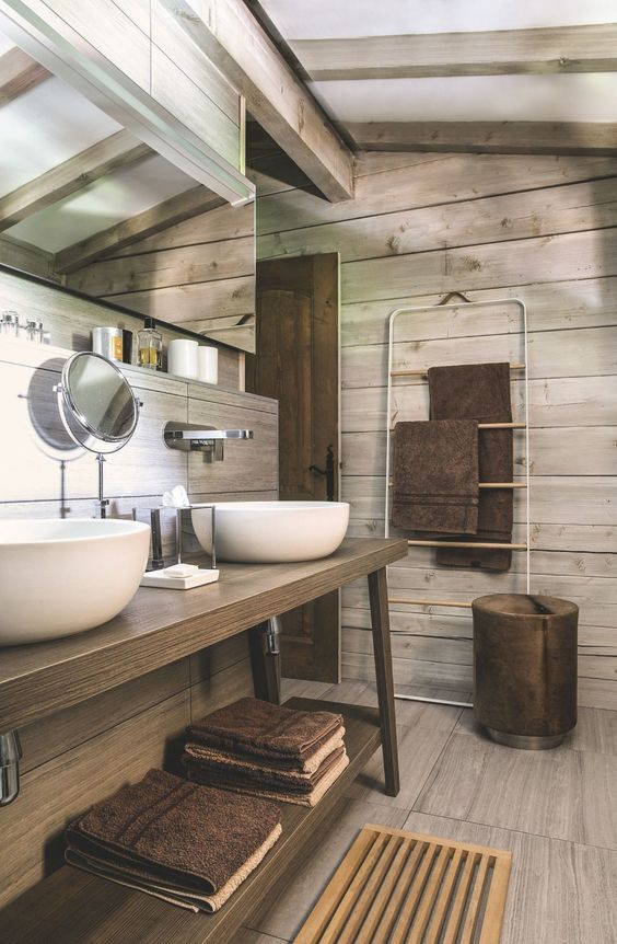 a cozy minimalist chalet bathroom clad with grey wood and matching tiles, a table vanity, a mirror and a modern stool