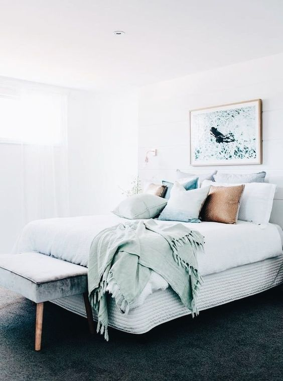 a cute coastal bedroom in neutrals, with seaside-inspired bedding and an artwork is very welcoming