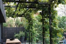 a dark and modern backyard with a wooden dining table, black wicker chairs and greenery over black metal beams