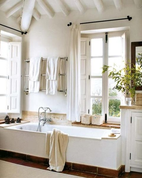 a farmhouse bathroom in white, with wooden beams on the ceiling, a large tub, some tiles and wood plus windows with shutters