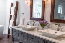a farmhouse bathroom with a vintage blue vanity, wood frame mirrors, sconces, baskets and a ladder with towels
