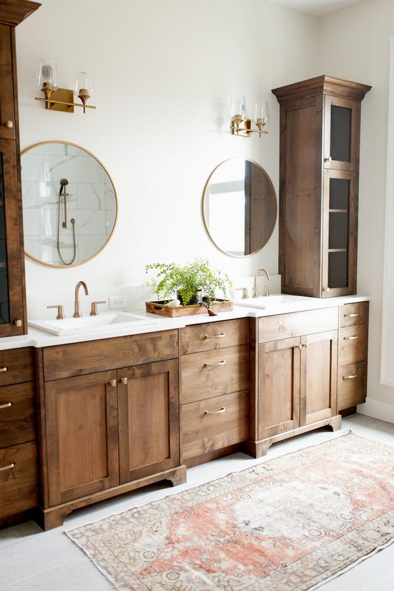 a farmhouse bathroom with dark stained furniture, round mirrors and chic sconces for a vintage feel