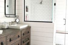 a farmhouse bathroom with white tiles and beadboard, printed tiles on the floor, a wooden vanity and vintage mirrors