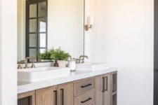 a farmhouse bathroom with white walls, a floating wooden vanity and a large statement mirror plus greenery