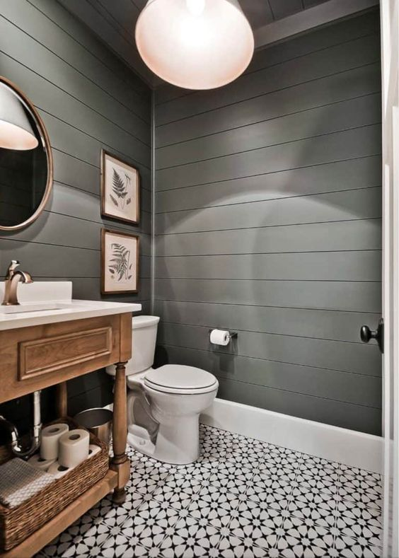 a farmhouse powder room with grey beadboard walls, a pendant lamp, a tile floor and a vintage wooden vanity plus artworks