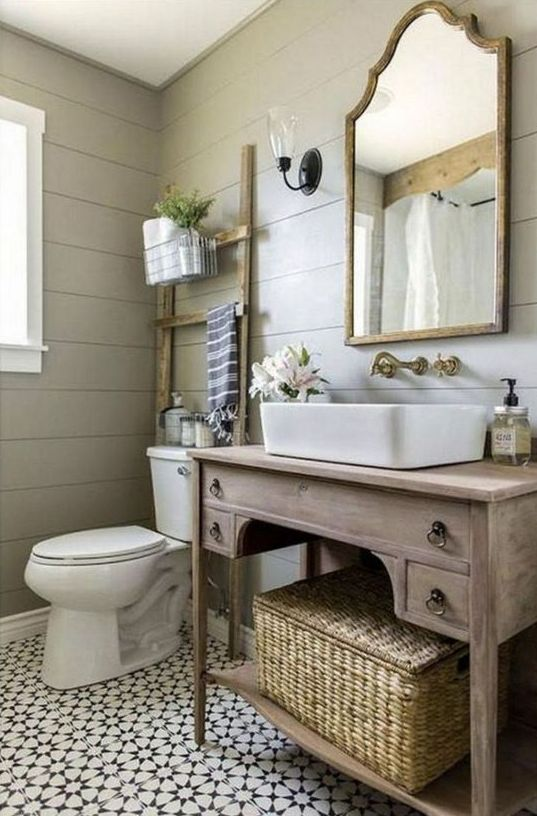 a farmhouse powder room with grey beadboard walls, a wooden vanity, a mirror in a wooden frame and vintage fixtures