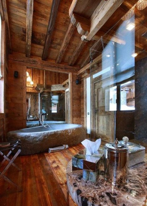 a gorgeous chalet bathroom clad with rich stained wood, a stone tub, a shower space and a stone table