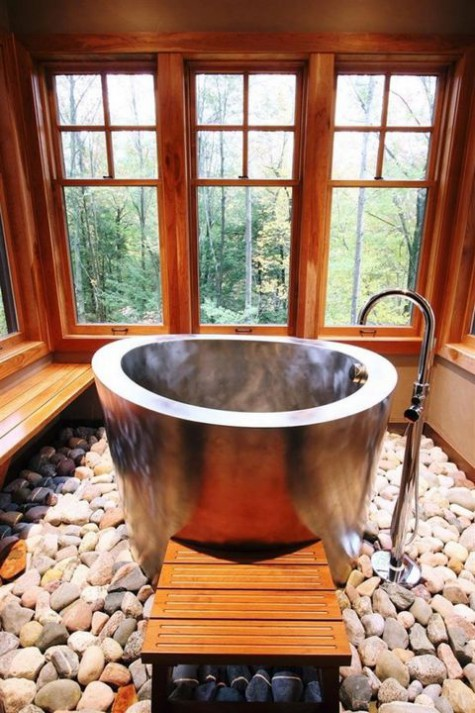 a gorgeous chalet bathroom clad with rich-stained wood, with windows for amazing views, a metal ofuro tub and rocks on the floor