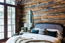 a gorgeous chalet bedroom clad with reclaimed wood, with a statement sphere and crystal chandelier and lots of faux leather and fur