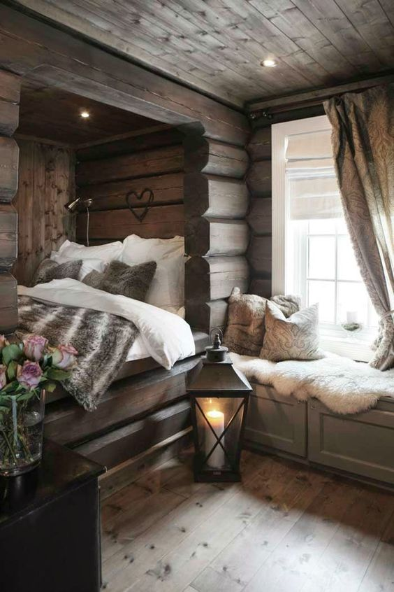 a gorgeous chalet bedroom clad with wood, with a bed in a niche, a windowsill bench with storage is super welcoming