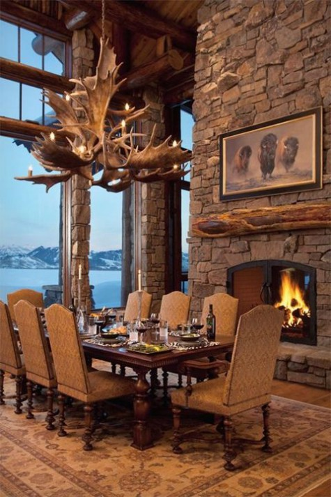 a gorgeous chalet dining room with a built-in fireplace, vintage furniture, an antler chandelier and a fantastic view of the mountains