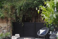 a laconic modern backyard with white gravel, a black fire pit, woven chairs, potted greenery and other plants