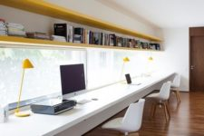 a large minimalist home office with bright yellow shelves, a long floating desk, white chairs and yellow lamps
