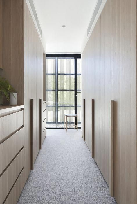 a light-colored wooden minimalist closet with large doors with handles and sleek drawers filled with light