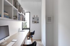 a long and narrow shared minimalist home office with a floating desk, open shelves, black chairs and a grid