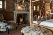 a luxurious chalet bedroom all clad with wood, with a canopy bed, a fireplace, a large mirror, faux fur covered furniture
