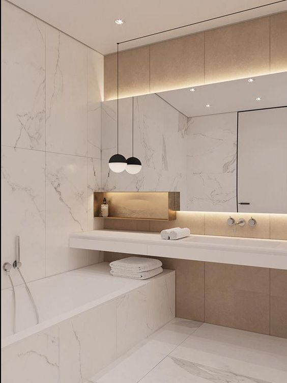 a luxurious minimalist bathroom with white marble large scale tiles, plywood panels, a large lit up mirror and a pendant lamp