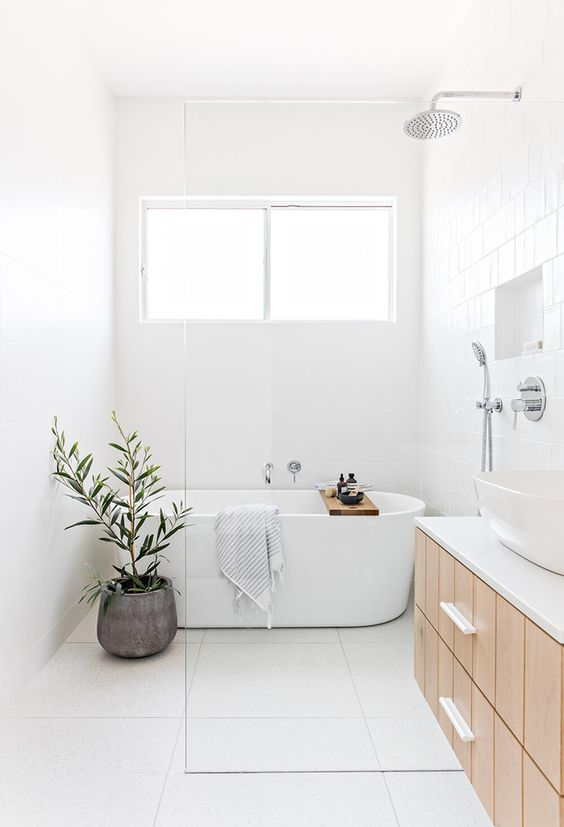 a minimalist airy bathroo with white tiles everywhere, a wooden vanity, a bathtub, a potted plant and a white sink