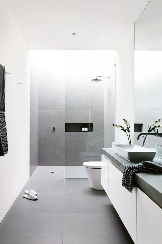 a minimalist bathroom clad with grey and white tiles, a floating vanity, a concrete countertop and a large mirror