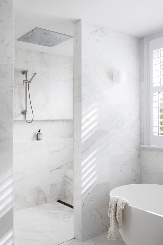 a minimalist bathroom clad with white marble tiles, a shower space and a bathtub is a chic space