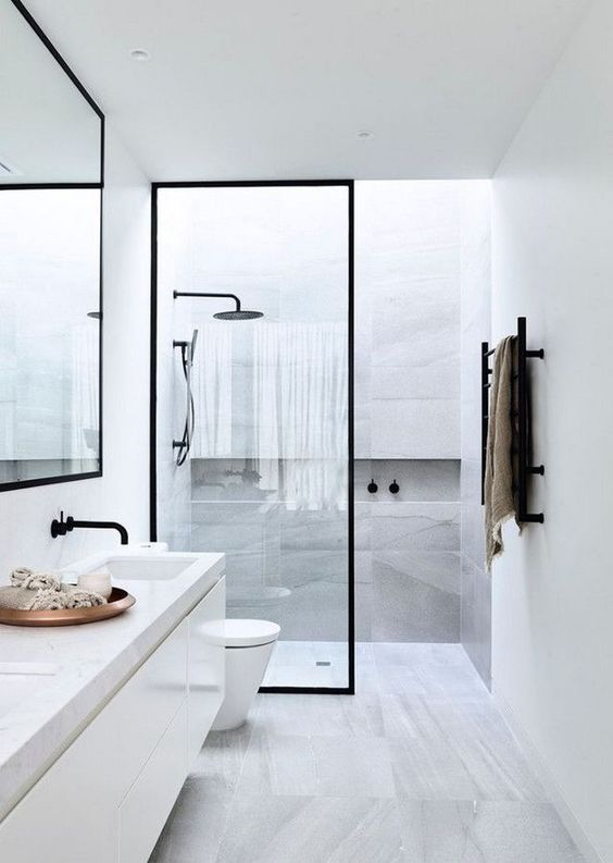 a minimalist bathroom in grey and white, with a skylight, a floating vanity, a mirror and touches of black for a cool look