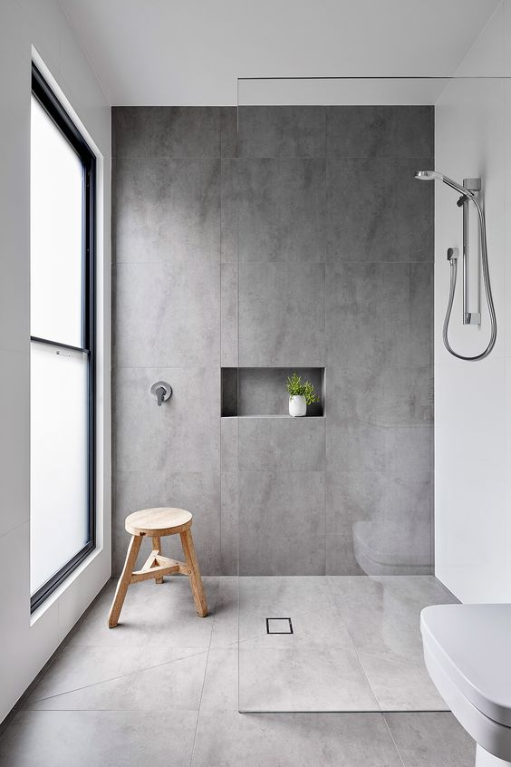 a minimalist bathroom with grey and white large scale tiles, a frosted glass window and simple fixtures