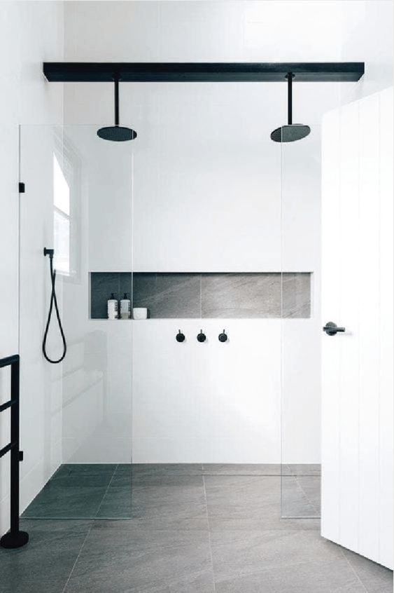 a minimalist bathroom with grey tiles on the floor, white tiles on the walls, black fixtures for a more catchy look