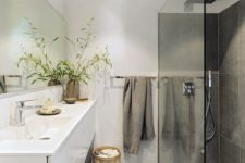 a minimalist bathroom with large scale grey tiles, a shower space, a floating white vanity, white walls and a large mirror
