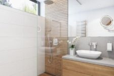 a minimalist bathroom with neutral tiles, sleek wooden touches, a cocnrete wall, a large mirror and a small window