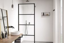 a minimalist bathroom with neutral walls, a concrete floor, a simple vanity, a mirror and a pendant bulb