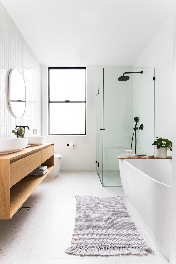 a minimalist bathroom with skinny tiles on the wall, neutral tiles on the floor, a glass enclosed shower space, a bathtub and a floating vanity