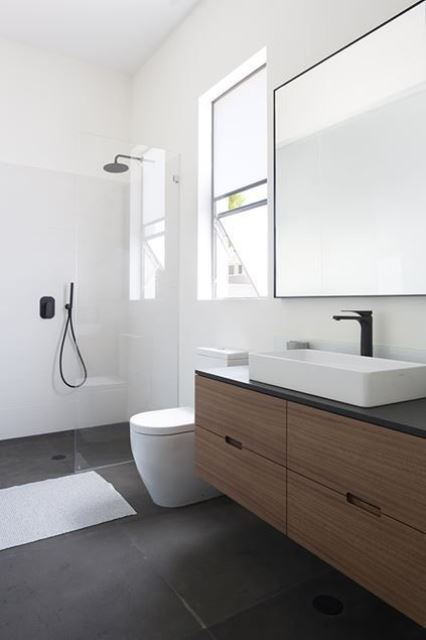 a minimalist bathroom with white walls, dark tiles on the floor, a wooden vanity, catchy appliances and a mirror