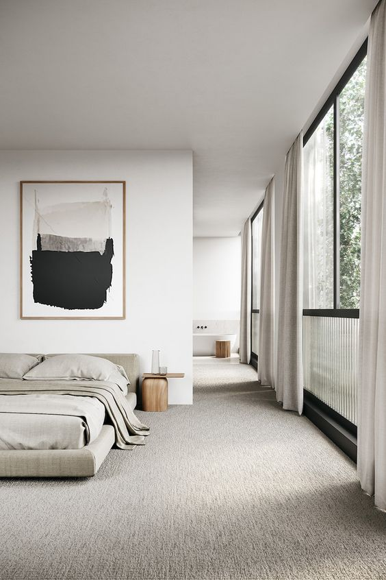 a minimalist bedroom in neutrals with an upholstered bed, wooden nightstands, a statement artwork and a large window