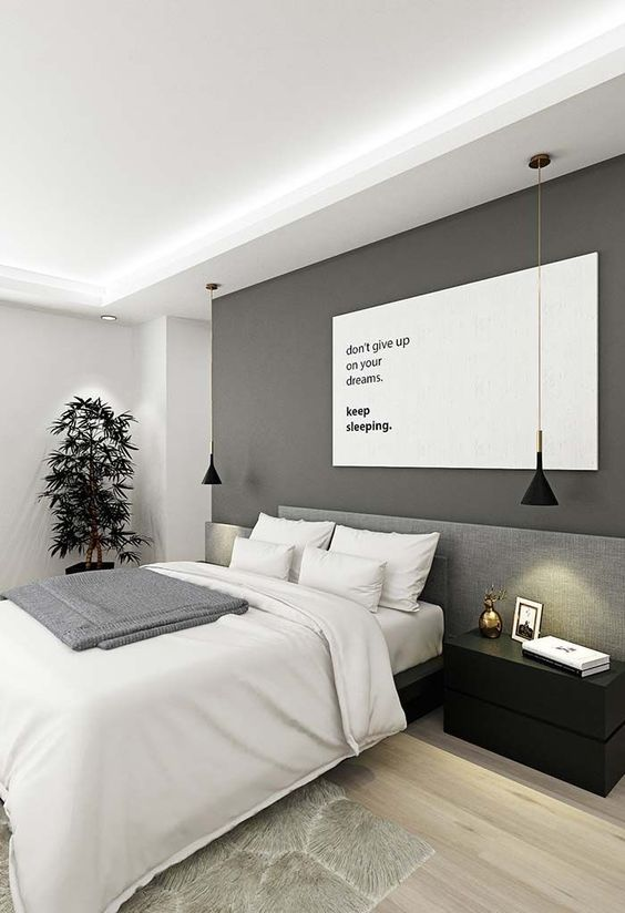 a minimalist bedroom with a grey accent wall, a bed with an upholstered headboard, black nightstands and pendant lamps