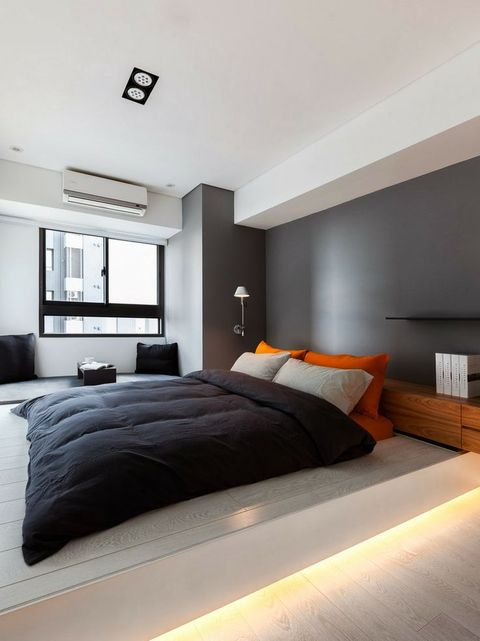 a minimalist bedroom with a grey accent wall, a platform bed with built-in lights, lamps and black and bright textiles