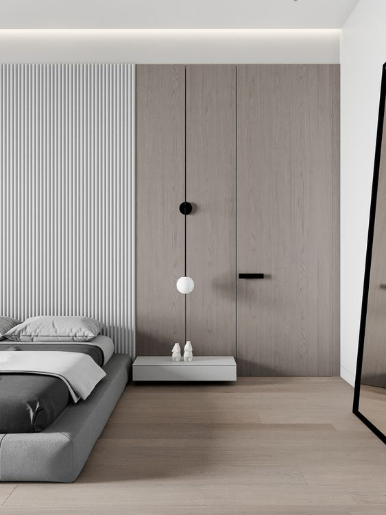 a minimalist bedroom with a plywood and wood slab wall, a grey upholstered bed, a white floatign nightstand and some lamps