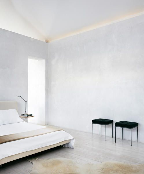 a minimalist bedroom with off-white walls, a wooden bed with an upholstered headboard, nightstands and black leather stools