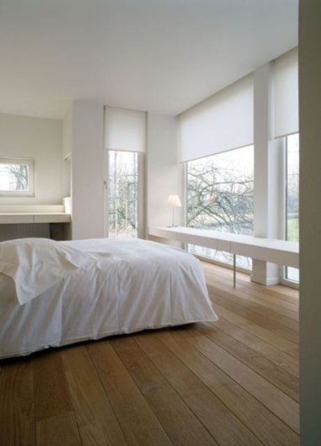 a minimalist bedroom with several windows, a sleek white vanity or desk, a smaller vanity on the left and a bed