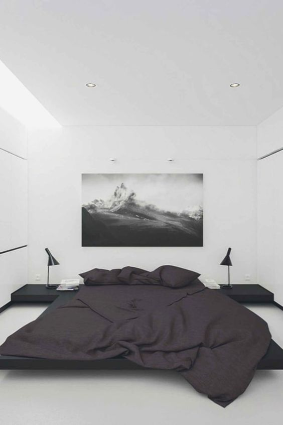a minimalist bedroom with white walls, a black bed and nightstands plus lamps and a statement artwork