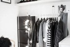 a minimalist black and white closet with open shelves, a holder with hangers, a sideboard, lights and touches of black