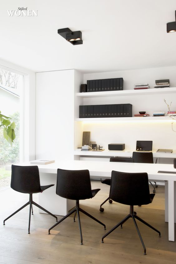 a minimalist black and white home office with open shelves, a desk and a meeting table with black chairs